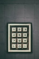 Vintage weathered keypad with reset and number buttons on a dark grey wall