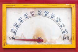 Vintage weathered meter with red needle in a red casing with yellow frame