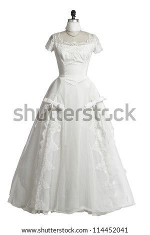Vintage wedding dress of ivory tulle over satin with empire neckline, lace cap sleeves, princess waist, and fitted bodice. Displayed upright on stand. White background, cut out, vertical, copy space.
