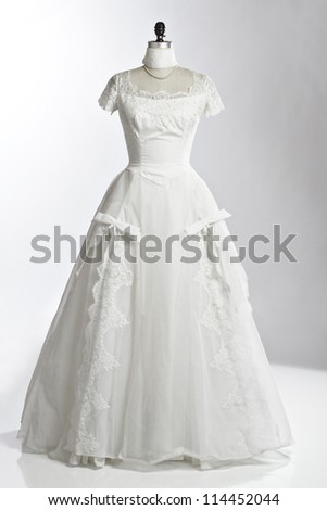 Vintage wedding dress of ivory tulle over satin with empire neckline, lace cap sleeves, princess waist, and fitted bodice. Displayed upright on stand. White background, vertical, copy space.