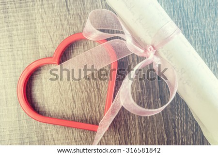 Vintage wedding invitation with pink ribbon and a red heart. Cross processed image with selective focus