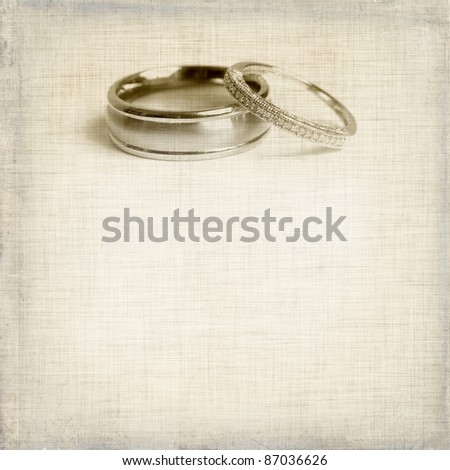 stock photo vintage wedding invitation with two rings on sepia textured