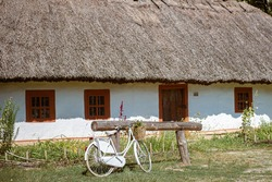 Vintage white bicycle decorated with flower basket standing beside old Ukrainian house with hay roof
