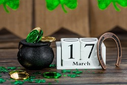 Vintage white calendar for St. Patrick's Day, March 17, with a lucky horseshoe and a pot of gold on a wooden background.