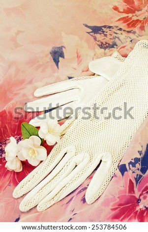 Vintage white gloves and artificial flowers of jasmine on flowered silk