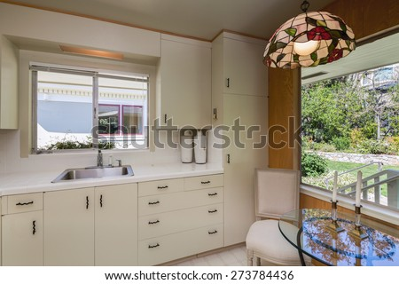 Vintage white kitchen with Light Pendant in bronze and colored glass with view window to garden.