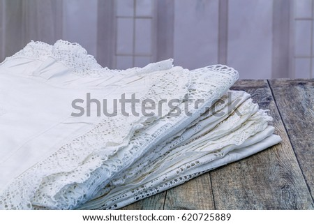 Vintage white lace bed linen on grey wooden surface on window background, close up #620725889