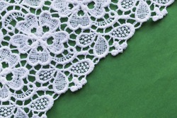 Vintage white lace on green background closeup