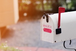 Vintage white mailbox for mailing communications outside the door of house.