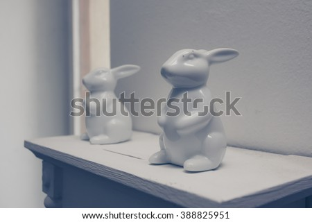 Vintage white porcelain easter rabbits standing on white shelf.