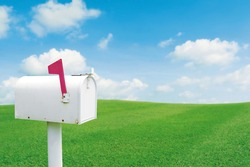 Vintage white post mailbox with blured outdoor green lawn grass and blue sky