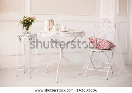 Vintage White Room With Chair And Table With Flowers Pillow, Coffee Cups And Candles