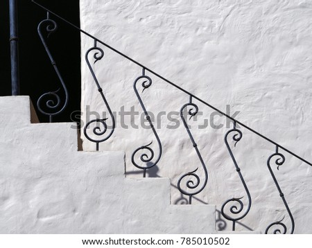 Vintage white wall stairs with metal railings.