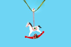 Vintage white wooden rocking horse, Christmas tree decoration. Toy for the Christmas tree. Minimal concept of Christmas or New year.