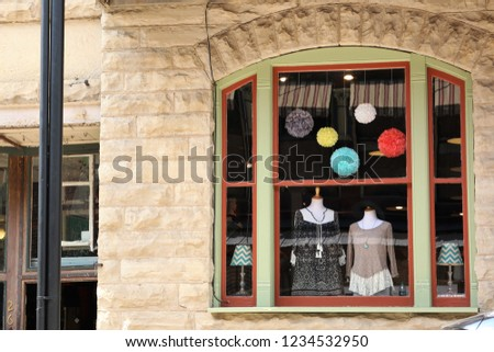 Vintage window of a boutique with two women blouses and tops on display on a mannequin and colorful pom pom decoration. Beige brick wall. Small business feel.