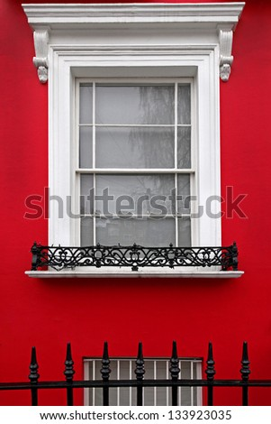 Vintage window on house with red facade