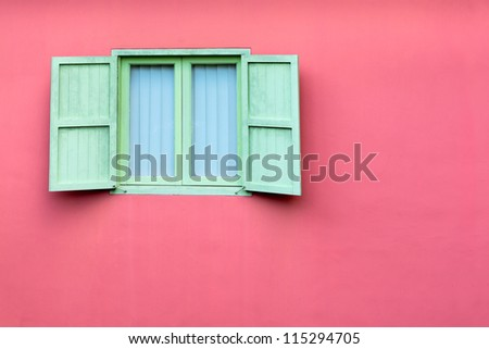 Vintage window with green retro wooden shutters on pink wall, Singapore