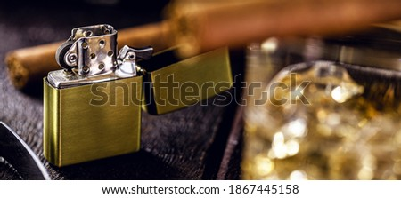 vintage windproof lighter on rustic wooden background. Cigar accessory, luxury concept, male gift ストックフォト ©