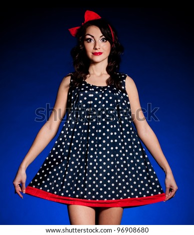 Vintage woman in retro dress on dark background. Pin-up girl