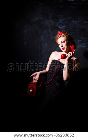 Vintage woman using a retro red phone
