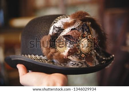 Vintage women's Victorian steampunk hat. Trim: lace, fur, gears, brooch cameo. On dark background #1346029934