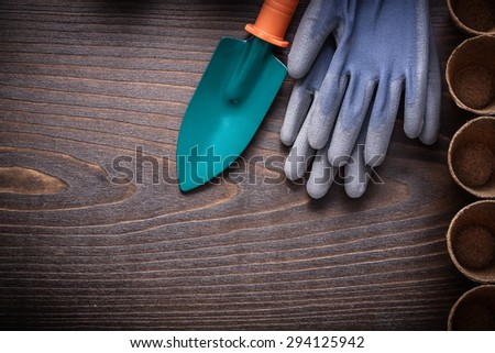 Vintage wood board with protective gloves variety of peat pots and hand spade gardening concept.