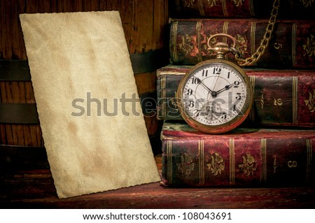 Vintage wood desk with old photo paper texture, books and old pocket clock in low-key. Concept of time,the past or deadline.