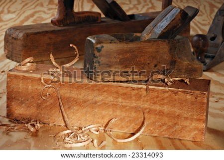 Vintage wood planes with block of wood and shavings in warm sunlight. - stock photo