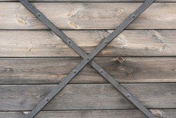 Vintage wood texture of boards with a metal crosshair connecting them. form of X