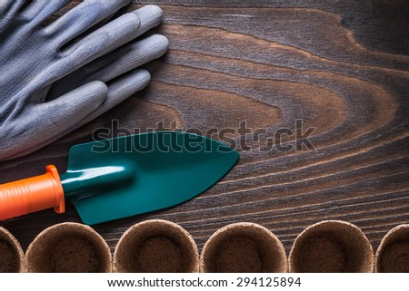 Vintage wooden board with rubber gloves peat pots and hand shovel gardening concept.