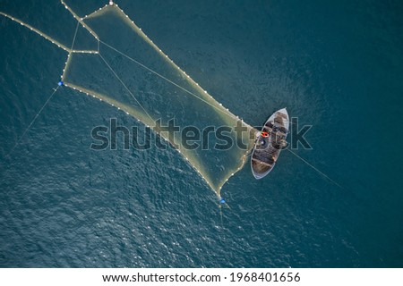 Vintage wooden boat in coral sea. Boat drone photo. A fisherman on a fishing boat is casting a net for catching fish. Сток-фото ©