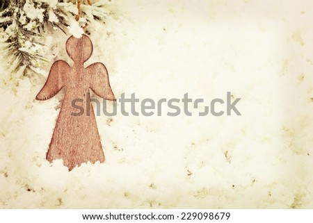 Vintage wooden Christmas angel decoration on snow background