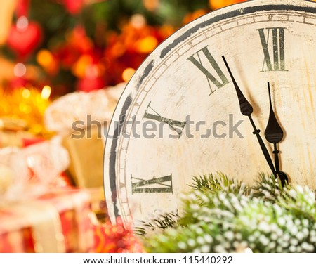 Vintage wooden clock against Christmas lights background. New year concept