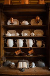 Vintage wooden cupboard with dishes in Victorian kitchen.