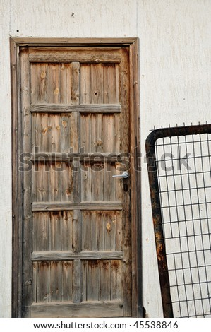 Vintage wooden door and rusty metal fence.