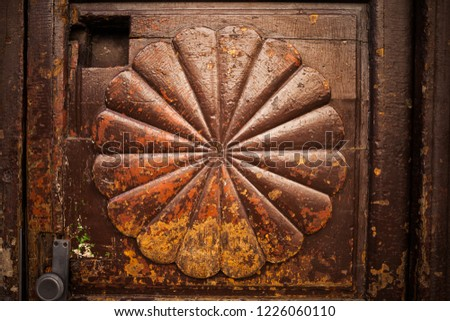Vintage wooden door with abstract radial fan shape or flower petals, retro grunge look, peeling and flaking brown paint with yellow and orange accents.