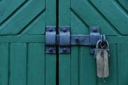 Vintage wooden green doors gates closed with metall padlock with hasp