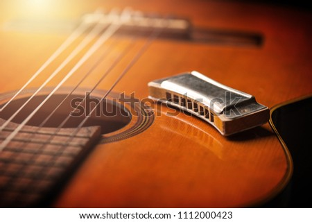 vintage wooden harmonica lying on an old acoustic guitar. - Shutterstock ID 1112000423
