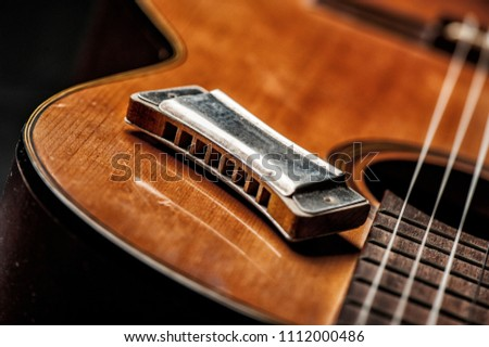 vintage wooden harmonica lying on an old acoustic guitar. - Shutterstock ID 1112000486