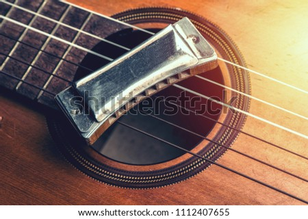 vintage wooden harmonica lying on an old acoustic guitar. - Shutterstock ID 1112407655