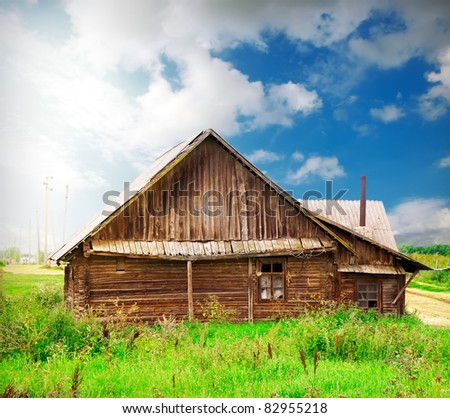 vintage wooden house in the countryside over blue sky with artistic lights and shadows added
