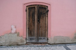 Vintage wooden painted door of old building. Shabby door boards. Old wall made of pink plaster and gray putty stains on the wall. Smooth surface. Cracks. Old peeling plaster wall, crumbles.
