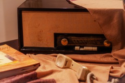 Vintage wooden radio covered in cream-colored fabric,80'-90's phone handset and photo album. Presentation of antique,retro music,communication devices.