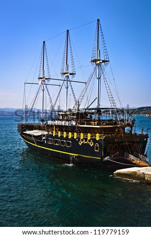 Vintage wooden ship sailing on the blue sea with blue sky