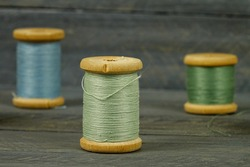 Vintage wooden spools of thread for sewing stand on dark wooden table