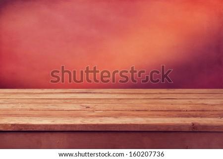 Vintage wooden table over grunge pink wallpaper background