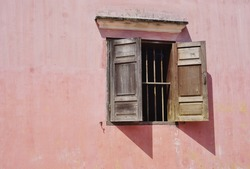 Vintage wooden window shutters cast abstract shadows on a faded pastel pink wall in rural Southeast Asia
