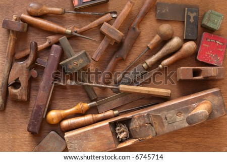 Vintage woodworking tools, including planes, chisels, whittling tools