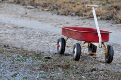 Vintage, worn little red wagon alone on a gravel road
