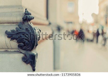 Vintage worn retro brass patina forged building corner decor element. Shallow focus. Copy space. Blurred background with busy Parisian street. Vintage effect.